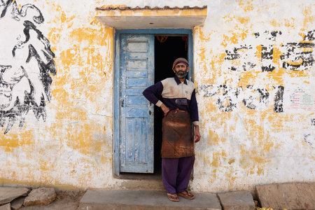 unfolding: BHUJ, INDIA - JANUARY 14: Man dealing with the dyeing of fabrics in the traditional way standing in the door of the manufacture in the  Gujarat state in India, Bhuj in January 14, 2015 Editorial