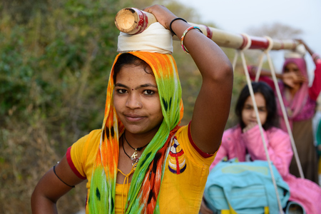 rajhastan: PALITANA, GUJARAT, INDIA - JANUARY 25: Indian woman which on the head is transporting pilgrims to the holy Palitana top in the Gujarat state in India, Palitana in January 25, 2015 Stock Photo