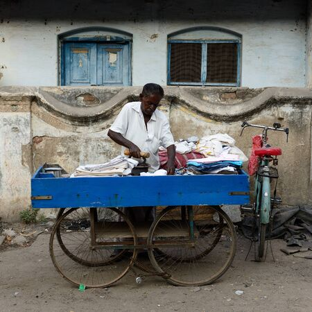 tamilnadu: MADURAJ, TAMILNADU, INDIA -MARCH 05: Indian ironing clothes in the street in India in Madurai city in the Tamilnadu state in India, Maduraj in March 05, 2015 Editorial