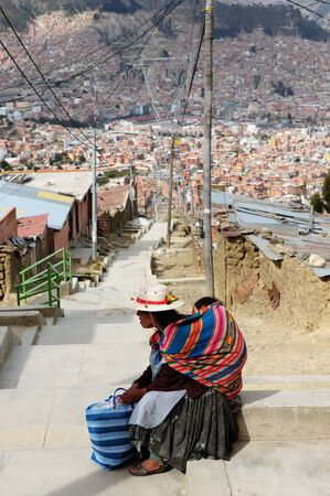 asl: View on the centre La Paz from poor districts put on the outskirts of town at 4000 m level asl. The woman is resting on the way to the city centre. Editorial