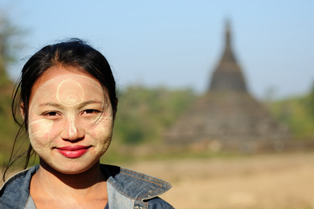 MRAUK-U, MYANMAR - JANUARY 24: Portrait of the Burmese woman in traditional make-up made of Murrays powdered wood, in the background Buddhist temples in Mrauk-U town on January 24, 2011