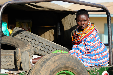 MARARAL, KENYA - JULY 03: African woman from the Samburu tribe with characteristic decorative necklaces is waiting for the transport by jeep to ones village in the bushon near the Mararal town in Kenya, Mararal in July 03, 2013