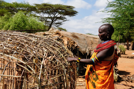 SOUTH HORR, KENYA - JULY 07: African woman  with characteristic decorative necklaces from the Samburu tribe in the traditional dress he is building his house in Kenya, South Horr in July 07, 2013