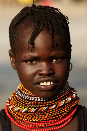 LOIYANGALANI, KENYA - JULY 14: Portrait african girl from the Turkana tribe in the traditional dress in transit to the market in Kenya,Loiyangalani in July 14, 2013