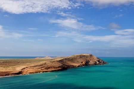 Colombia, Peninsula La Guajira. Caribbean coast with turquoise water and orange sand hill
