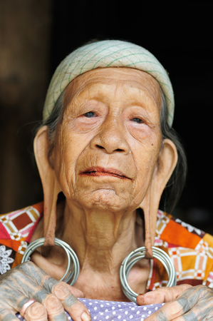 LONG BAGUN, BORNEO, INDONESIA - 10 JULY 2011: The older Dayak women with traditional long earlobes and tattoo from Borneo