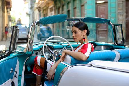 HAVANA, CUBA - 11 DECEMBER 2016: De mooie Cubaanse vrouw krijgt de klassieke Amerikaanse auto in het centrum van oud Havana op Cuba