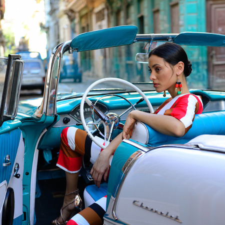 HAVANA, CUBA - DECEMBER 11: Cuban woman is getting a classical American car off in the center of old Havana Editorial