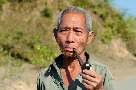 BAGAN, MYANMAR - 24 JANUARY 2011: Portrait of the Burmese smoking a pipe Editorial