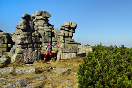 Hikings along tourist trails in the Karkonosze Mountain national park in Poland with the backpack on the back. Rock formation Czech stones