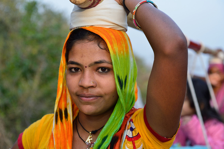 PALITANA, GUJARAT, INDIA - 25 JANUARY 2015: Indian woman which on the head is transporting pilgrims to the holy Palitana top in the Gujarat state in India Editorial
