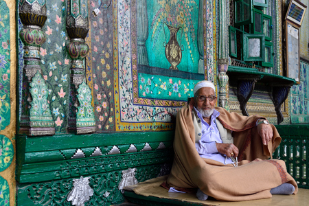 SRINAGAR, JAMMU AND KASHMIR, INDIA - 20 JUNE 2017: Muslim Imam welcoming faithful before the entry to a green uniquely wooden mosque, Shah E Hamdan