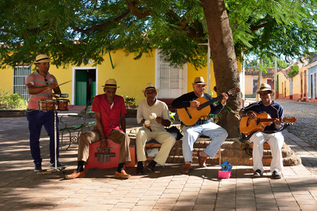 TRINIDAD, CUBA - 08 NOVEMBER 2016:  Latino American men of musicians play on maracases, guitar and small drums and sing songs on the square in Trinidad Editorial
