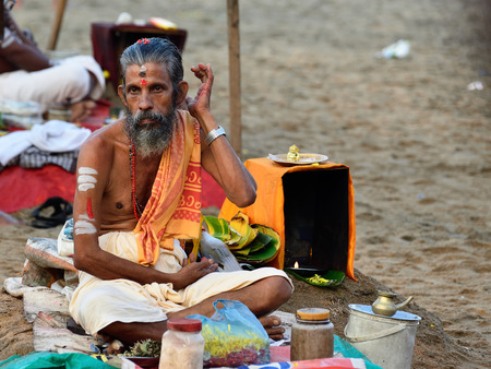 VARKALA, KERALA, INDIA - 18 MARCH 2015: Traditional morning Puja  in the holy place on Varkali beaches in the Kerala state in India. Brahmin waiting for pilgrims