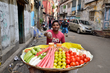 CALCUTTA, WEST BENGAL INDIA - 21 DECEMBER 2018: Seller of vegetables in of wicker basket on crowded streets of Calcutta in the West Bengal Editorial