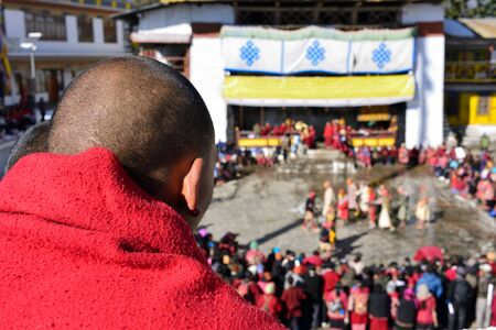 Tawang, Arunachal Pradesh, India, The Buddhist monk looking on the Torgya festival in the background there are monastery and many gathered viewers Stock fotó