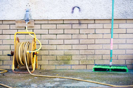 Yellow rubber hose and green sweep brush outdoors
