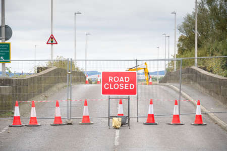 Road ahead closed sign with traffic cones and red barrier fence crossing