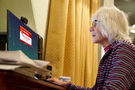Old elderly senior person with virus warning on computer monitor screen Stockfoto