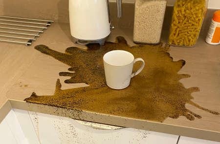 Spilt coffee drink and ground beans on kitchen worktop