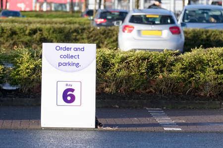 Click collect online internet shopping sign at shop car park lane