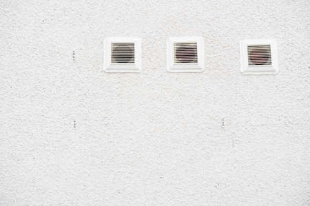 White plastic air vents on plain background house wall