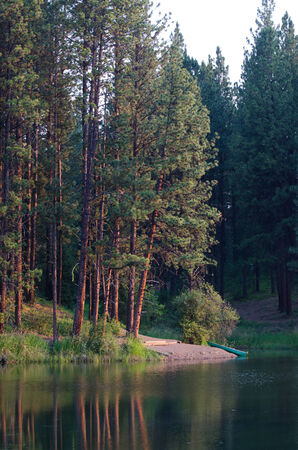 dawns: Canoe Resting on Remote Lake's Shore as Early Morning Dawns Stock Photo