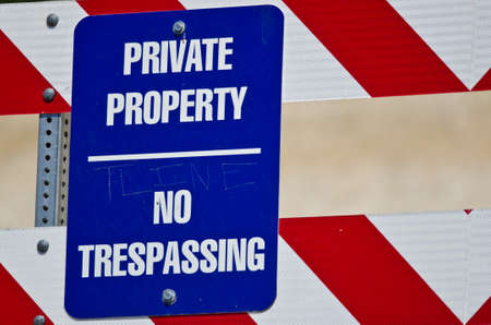 private property: Blue and White Private Property Sign on Construction Barricade