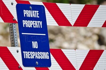 intruding: Blue and White Private Property Sign on Construction Barricade