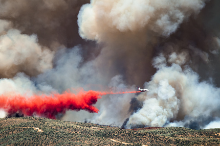 retardant: White Aircraft Dropping Fire Retardant as it Battles the Raging Wildfire