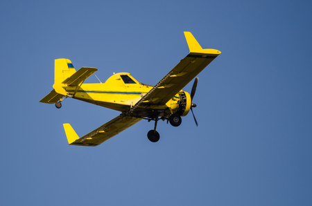 fertilize: Yellow Crop Dusting Plane Flying in a Blue Sky Stock Photo