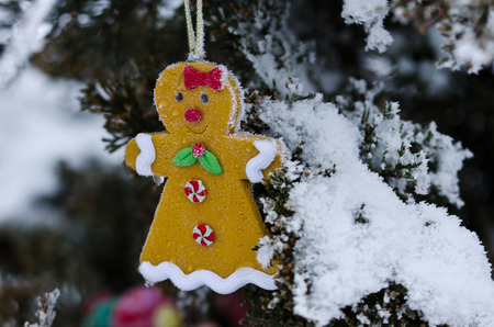 gingerbread woman decoration on a snowy outdoor christmas tree stock photo 62785348