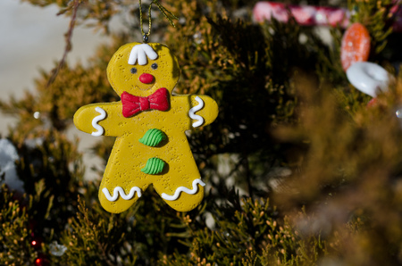 gingerbread man decoration on an outdoor christmas tree stock photo 65837021