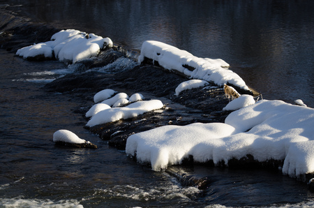 Snow Covered Rocks Forming Dam Across the Cold Winter River Stock Photo