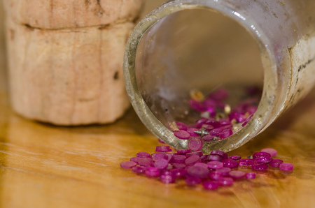 Watch Parts: Cap Jewels Spilling from Corked Vial Stock Photo