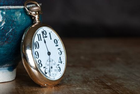 Vintage Golden Pocket Watch Resting on a Wooden Table Stock Photo
