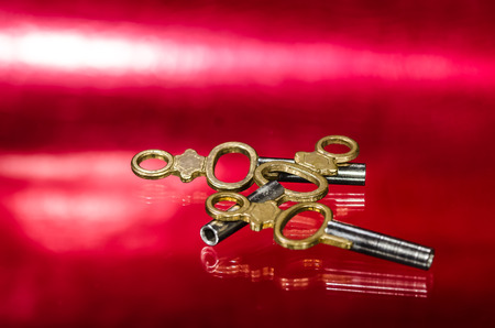 Three Antique Brass Pocket Watch Keys Laying on Red Surface