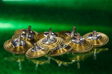 Watch Repair: Vintage Pocket Watch Fusee Cones Resting on a Green Surface Stock Photo