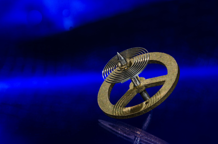 Watch Repair: Vintage Pocket Watch Hairspring Resting on a Blue Surface Stock Photo