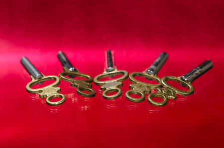 Five Antique Brass Pocket Watch Keys Laying on Red Surface