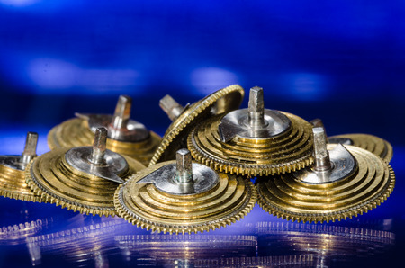 Watch Repair: Vintage Pocket Watch Fusee Cones Resting on a Blue Surface