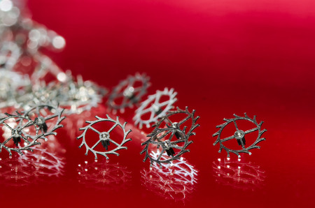 Watch Repair: Collection of Escape Wheels Resting in a Red Surface
