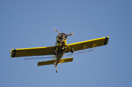 Yellow Crop Dusting Plane Flying in a Blue Sky Stock Photo