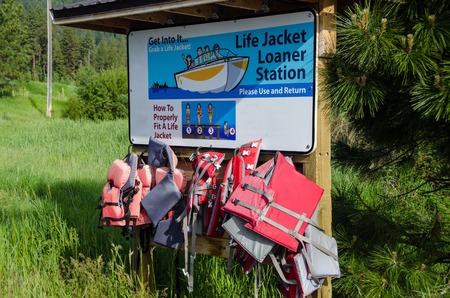 Life Jacket Loaner Station Beside the Summer Lake Stock Photo
