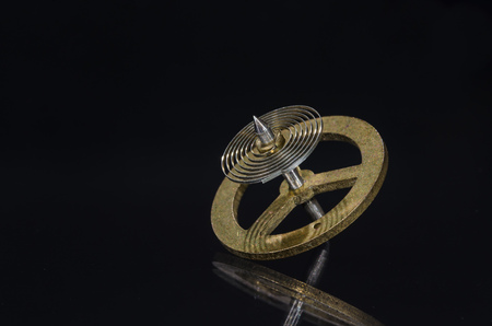 Watch Repair: Vintage Pocket Watch Hairspring Resting on a Black Surface Stock Photo