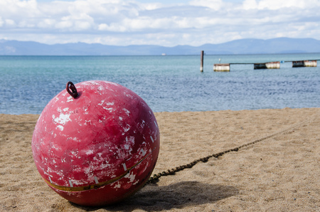 Red Buoy Pulled Onshore and Resting on the Sandy Beach
