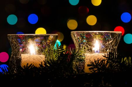 White Christmas Candles Surrounded by Christmas Lights and Evergreen Branches