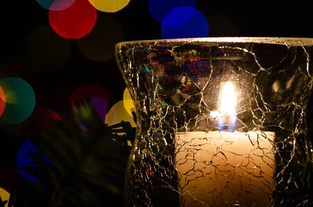 White Christmas Candle Surrounded by Christmas Lights and Evergreen Branches