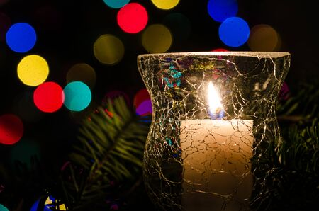 White Christmas Candle Surrounded by Christmas Lights and Evergreen Branches Reklamní fotografie - 127765010