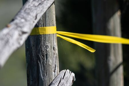 Yellow Barrier Tape Tied to an Old Weathered Fence Post Preventing Further Access Reklamní fotografie